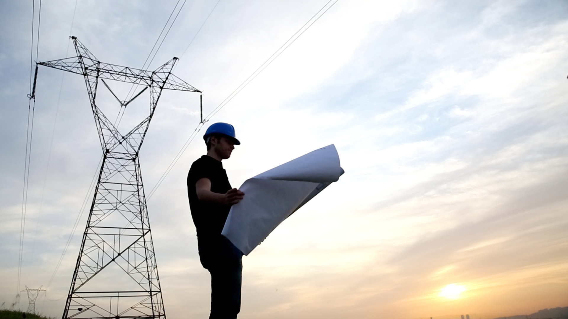 engineer holding blueprints under the power lines.